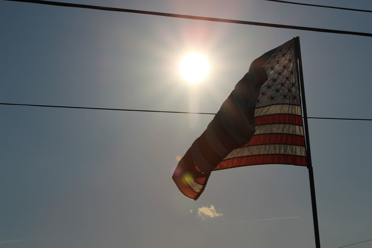 low angle view, flag, sun, patriotism, outdoors, sunset, sky, no people, day, nature, stars and stripes