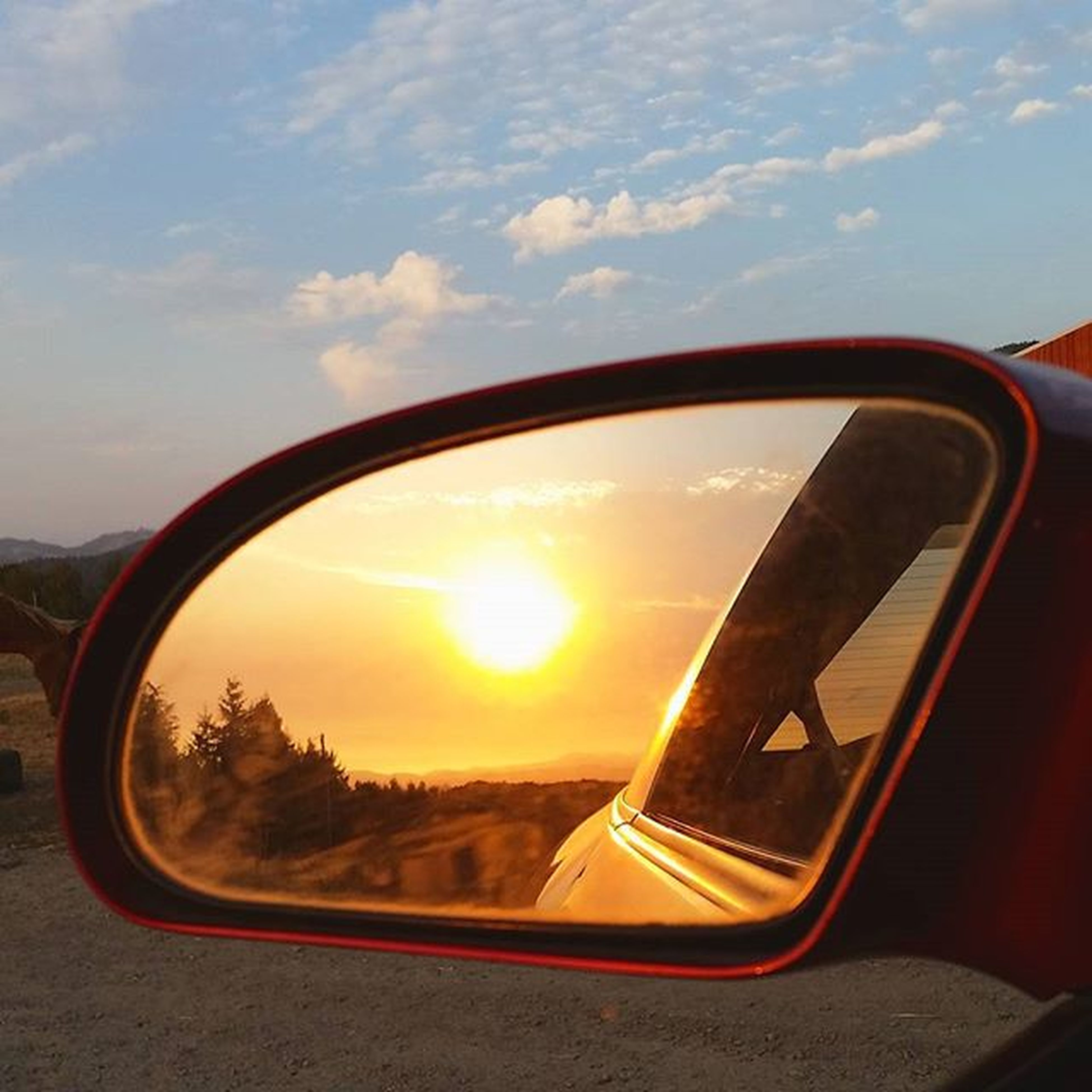 transportation, sunset, side-view mirror, mode of transport, sky, car, land vehicle, reflection, road, cloud - sky, vehicle interior, part of, glass - material, transparent, cloud, silhouette, close-up, orange color, travel, cropped