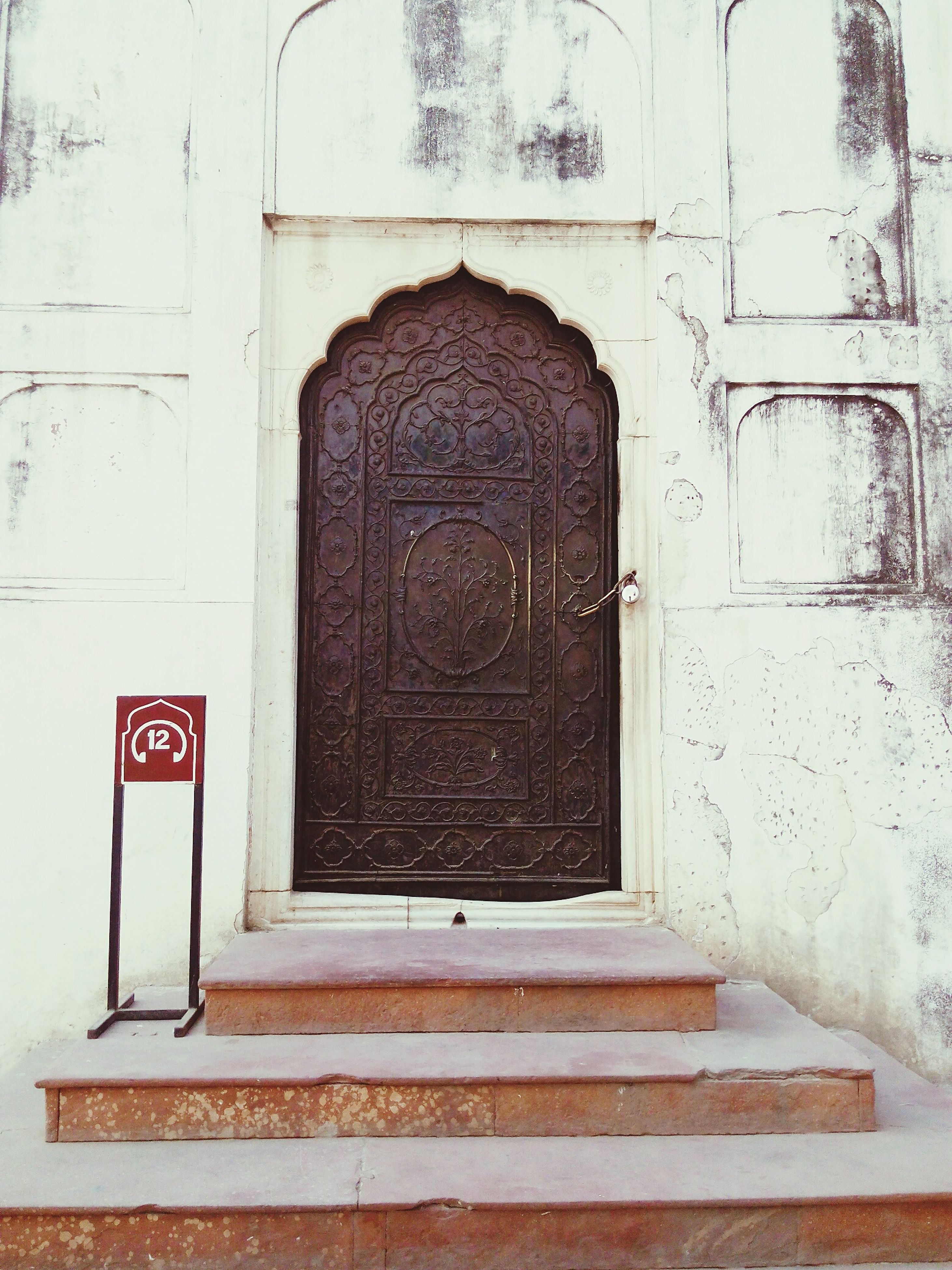 architecture, building exterior, door, built structure, closed, entrance, text, wall - building feature, communication, safety, western script, protection, outdoors, day, wall, facade, no people, old, security, red