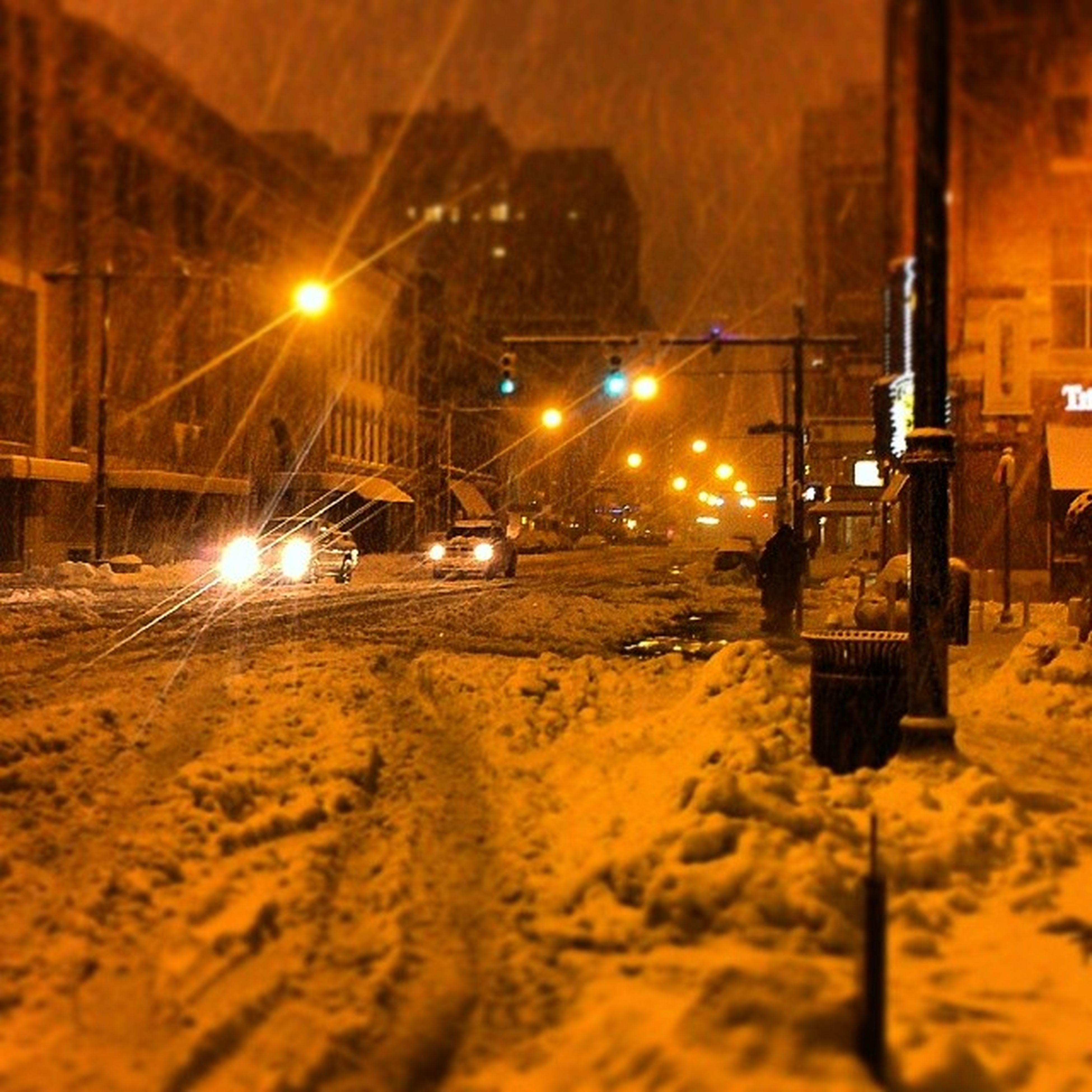 illuminated, transportation, night, street light, mode of transport, built structure, street, land vehicle, lighting equipment, architecture, building exterior, car, city, outdoors, road, snow, surface level, weather, season, no people