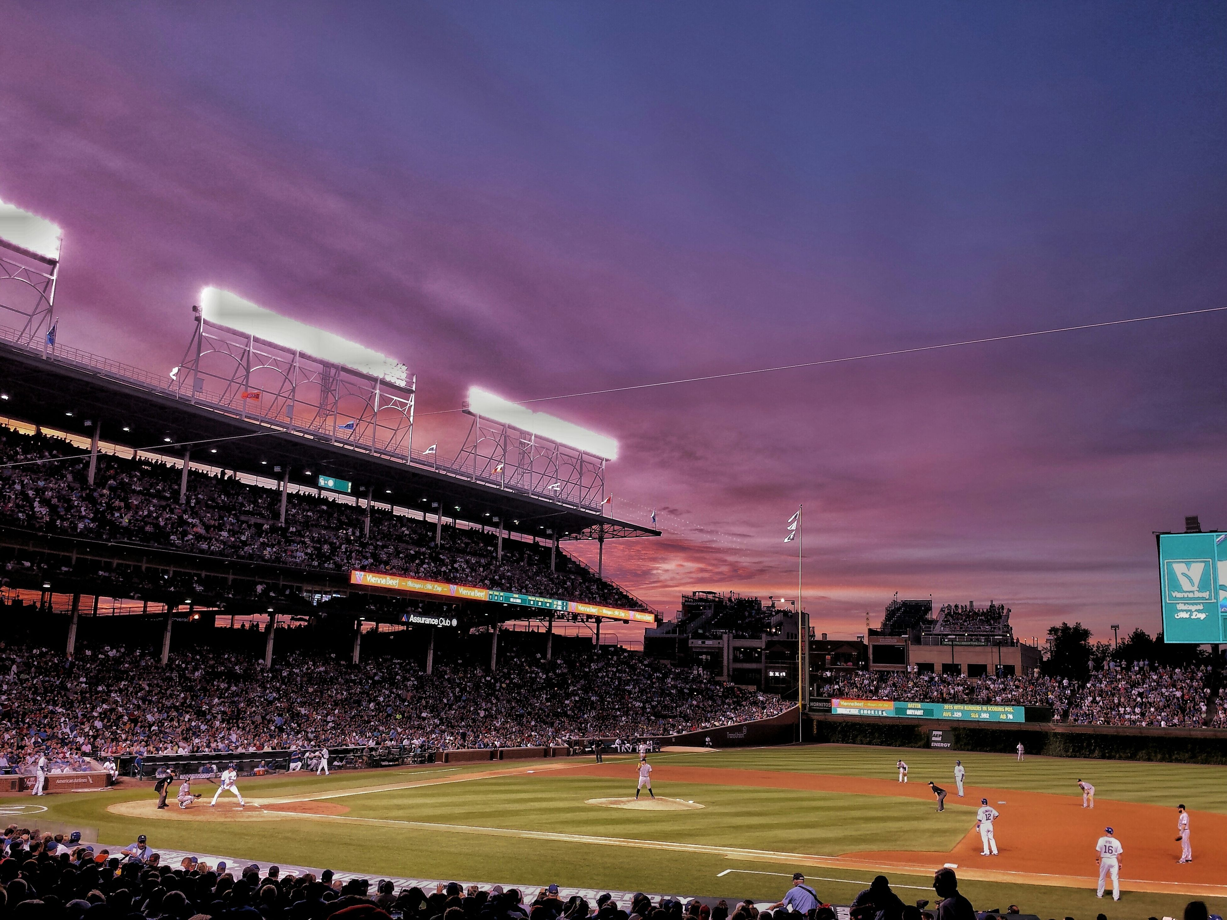 illuminated, night, building exterior, architecture, sky, built structure, large group of people, city, grass, cityscape, arts culture and entertainment, outdoors, city life, crowd, green color, cloud - sky, stadium, high angle view, lighting equipment, dusk