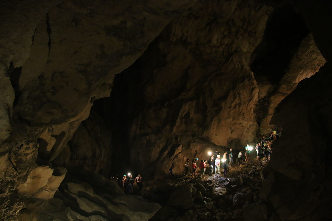 rock formation, cave, rock - object, geology, illuminated, real people, indoors, large group of people, leisure activity, physical geography, men, women, night, adventure, nature, people