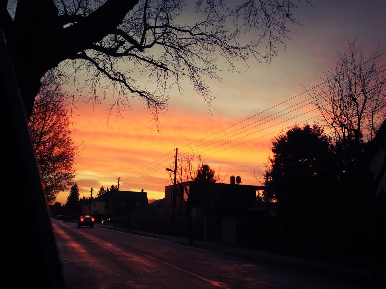sunset, silhouette, tree, sky, orange color, car, road, transportation, land vehicle, no people, built structure, cloud - sky, nature, beauty in nature, architecture, outdoors, bare tree, electricity pylon, building exterior, city