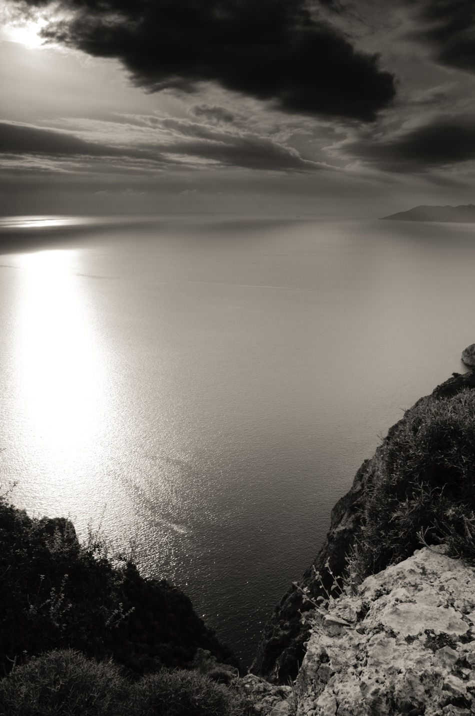 Peering over the top of a sheer cliff at a sea as smooth as butter and a moody sky hanging overhead Calm Sea Cliff Top View Cloudy And Moody Sky Day Hidden Sun Landscape Monochrome Shot Nature No People Outdoors Rocks Tranquil Scene Turkey