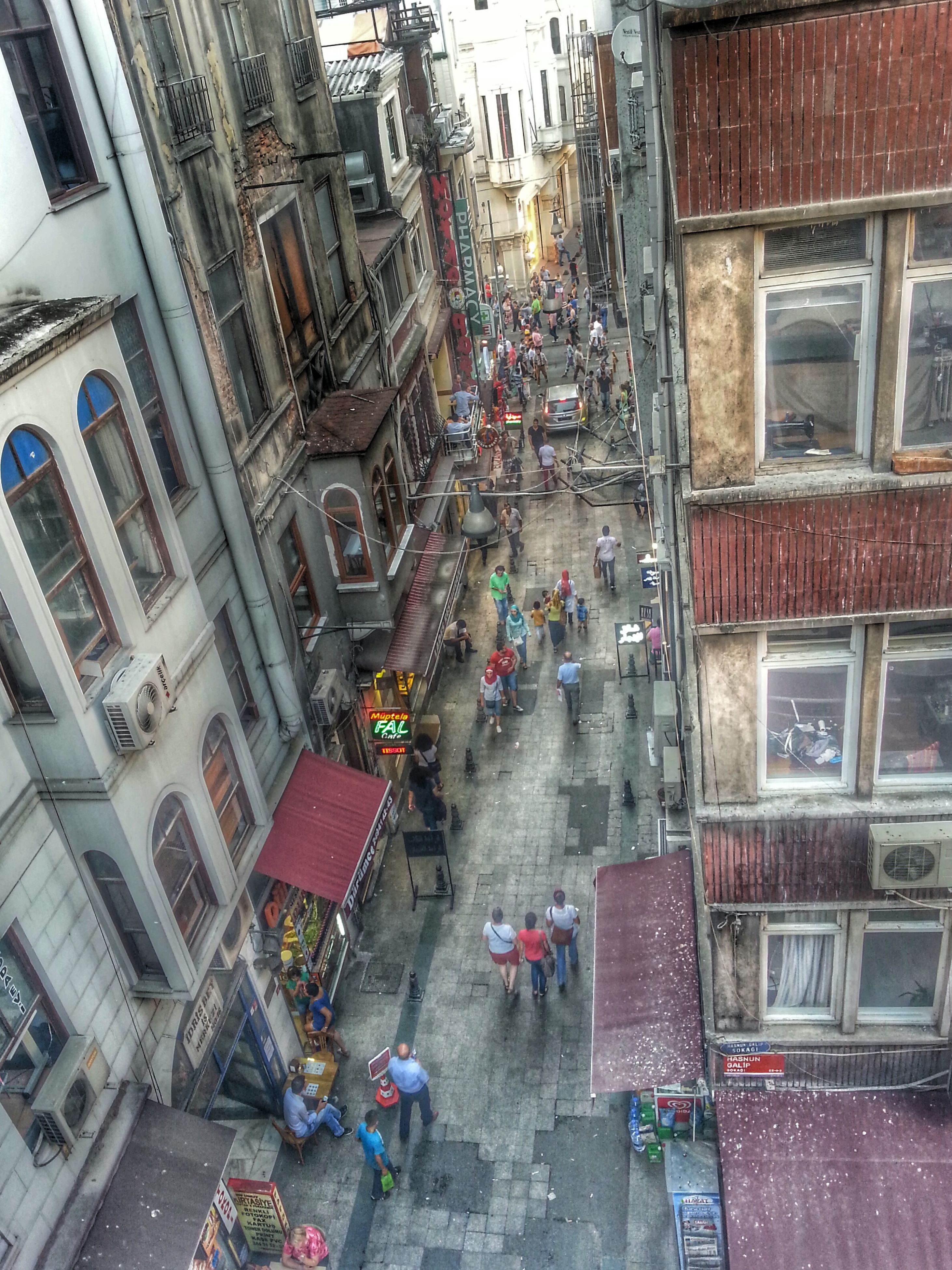 building exterior, architecture, built structure, city, street, building, city life, land vehicle, transportation, high angle view, residential building, city street, car, residential structure, mode of transport, window, road, incidental people, day