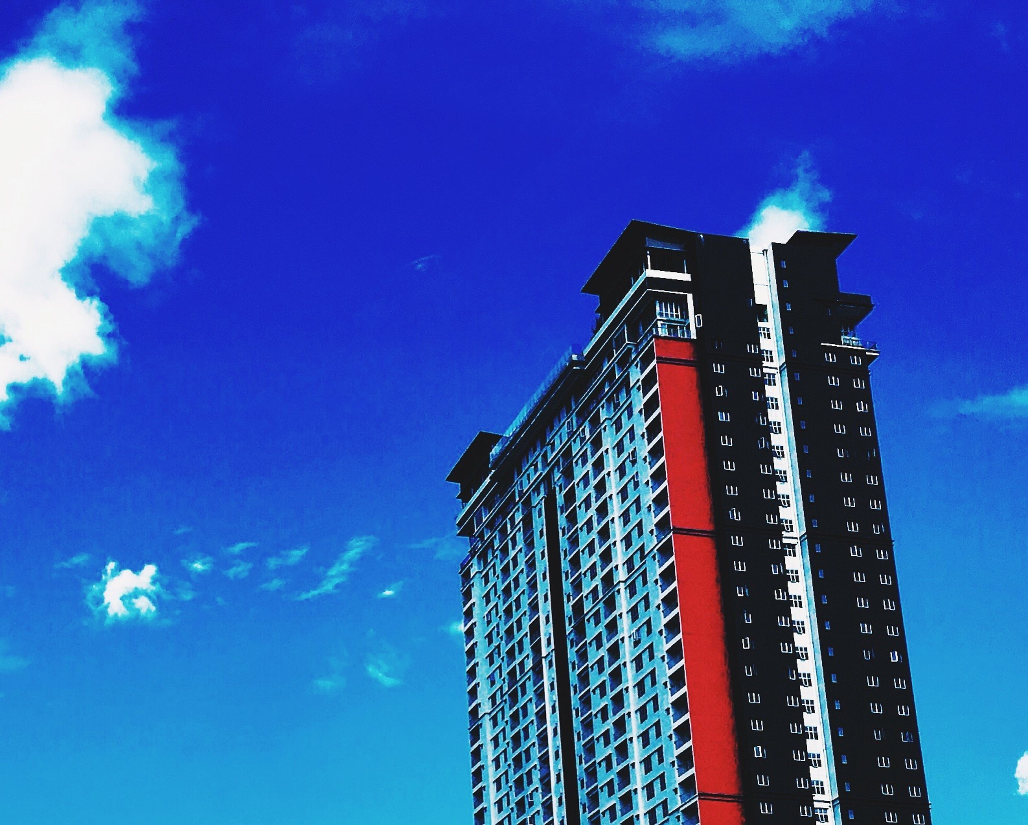 low angle view, blue, sky, built structure, architecture, building exterior, cloud - sky, tall - high, outdoors, tower, cloud, no people, day, dusk, sunlight, illuminated, lighting equipment, tall, high section, metal