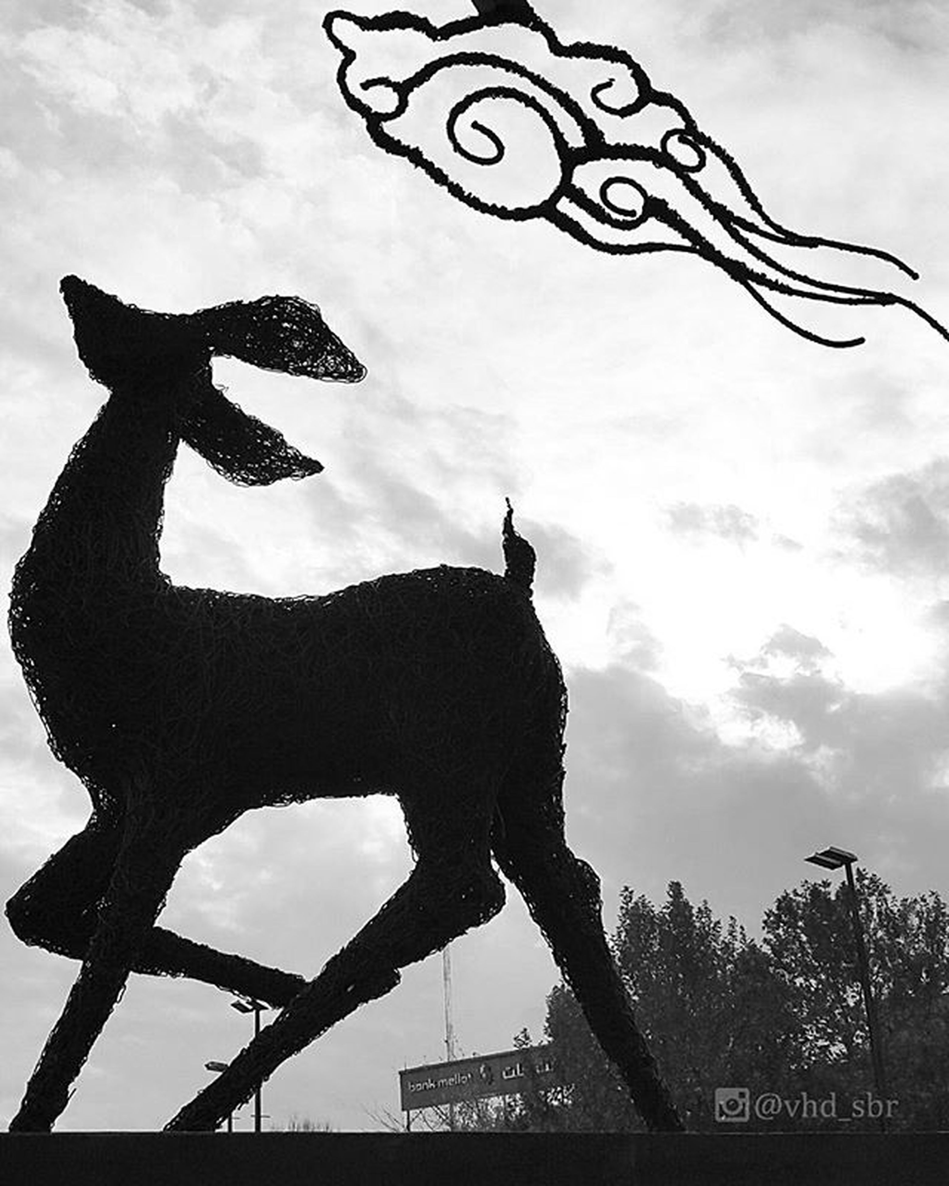low angle view, sky, animal representation, art and craft, cloud - sky, art, sculpture, statue, creativity, human representation, silhouette, animal themes, one animal, mammal, cloud, built structure, horse, tree, outdoors