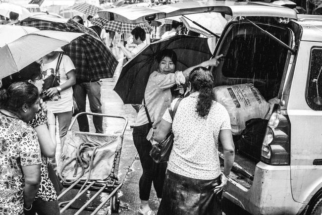 Collected Community loading clothes for a delivery in the rain