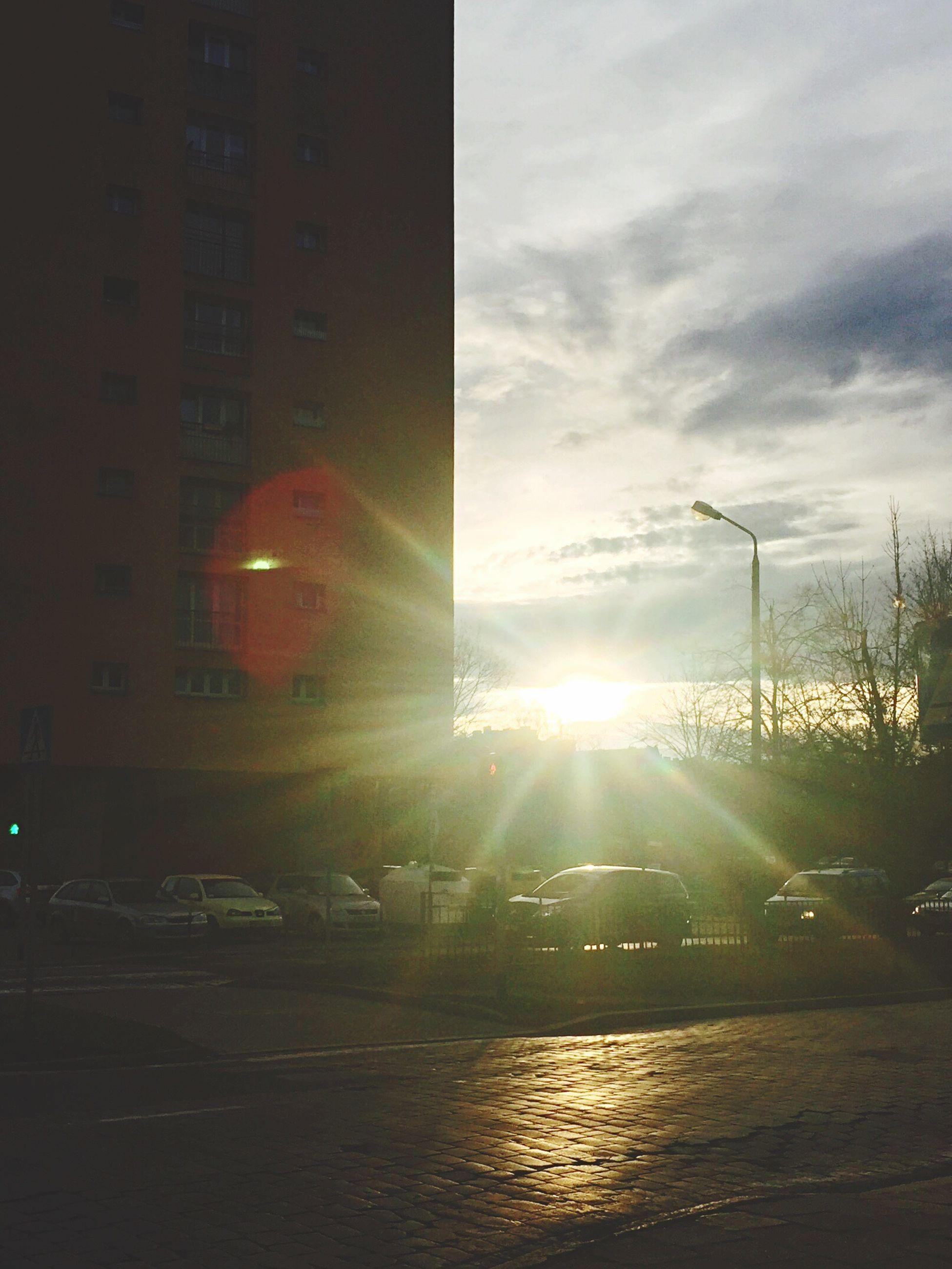 sun, transportation, building exterior, architecture, built structure, car, lens flare, sky, mode of transport, land vehicle, sunbeam, city, sunset, street, sunlight, street light, cloud - sky, road, reflection, city street