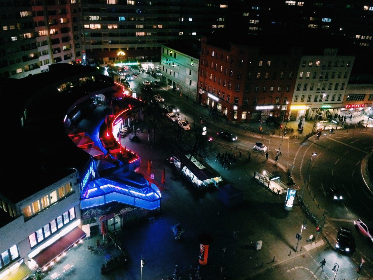city, building exterior, night, architecture, illuminated, street, high angle view, city life, built structure, cityscape, road, city street, outdoors, land vehicle, crowd, people