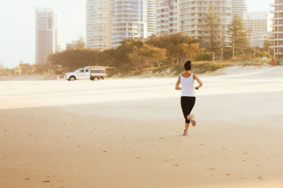 Adult Adults Only Athlete Beach City Day Exercising Full Length Healthy Lifestyle Jogging Lifestyles Motion One Person One Woman Only Only Women Outdoors People Running Self Improvement Sports Clothing Sports Training Vitality Young Adult