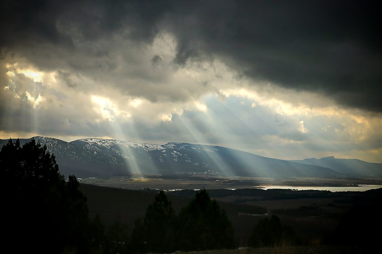 Beams of the sun make the way through clouds, against the background of mountains and lay down the surprising drawing on the valley. Beauty In Nature Cloud - Sky Day Dramatic Sky Landscape Light And Shadow Milky Way Mountain Nature No People Outdoors Scenics Sky Storm Cloud Sunbeam Travel Water