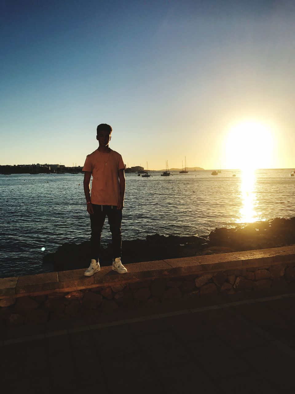 standing, water, full length, sea, sunset, one person, sunlight, sun, real people, nature, clear sky, outdoors, scenics, beauty in nature, tranquil scene, men, leisure activity, sky, lifestyles, horizon over water, vacations, one man only, day, people