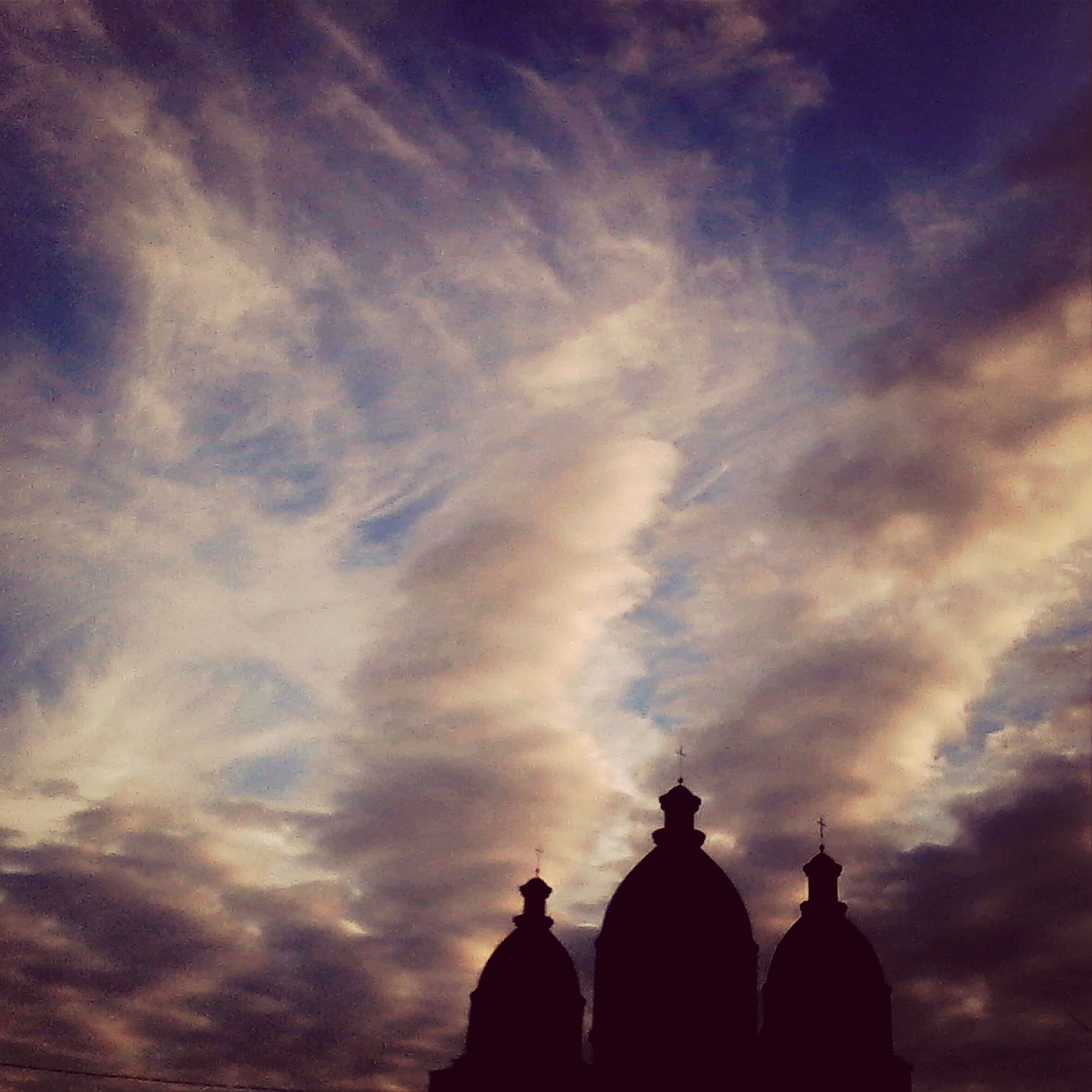 low angle view, sky, cloud - sky, silhouette, dome, architecture, cloudy, built structure, spirituality, place of worship, religion, sunset, cloud, famous place, high section, outdoors, sculpture, dusk, statue, travel destinations