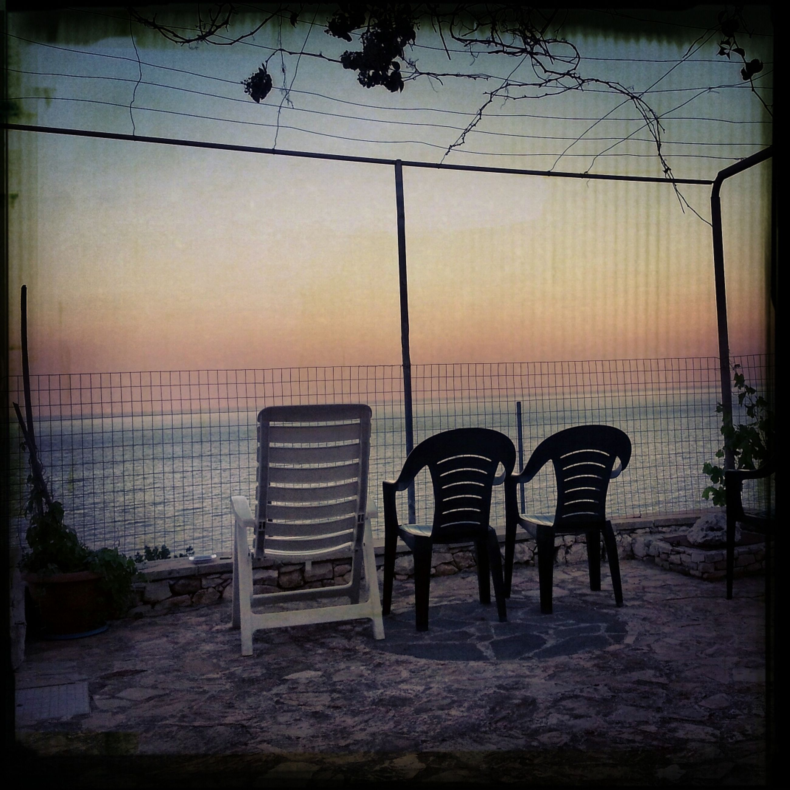 transfer print, auto post production filter, water, sea, sky, sunset, beach, built structure, chair, tranquility, nature, absence, tranquil scene, horizon over water, architecture, scenics, empty, outdoors, shore, no people