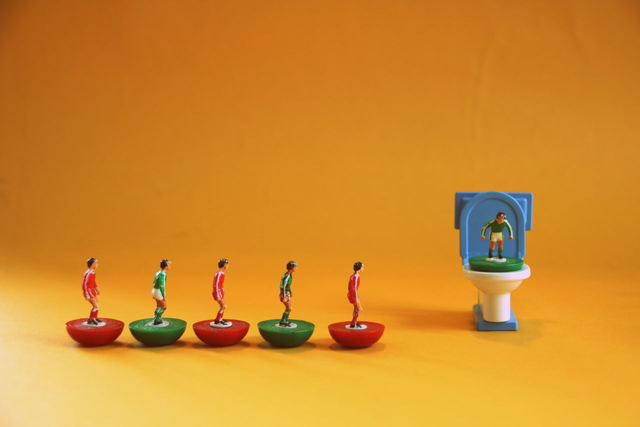 Close-up Closets Copy Space Day Figurine  Football Footballer Funny Funny Faces Green Color In A Row Indoors  Multi Colored No People Still Life Studio Shot Toy Wc Yellow Yellow Background