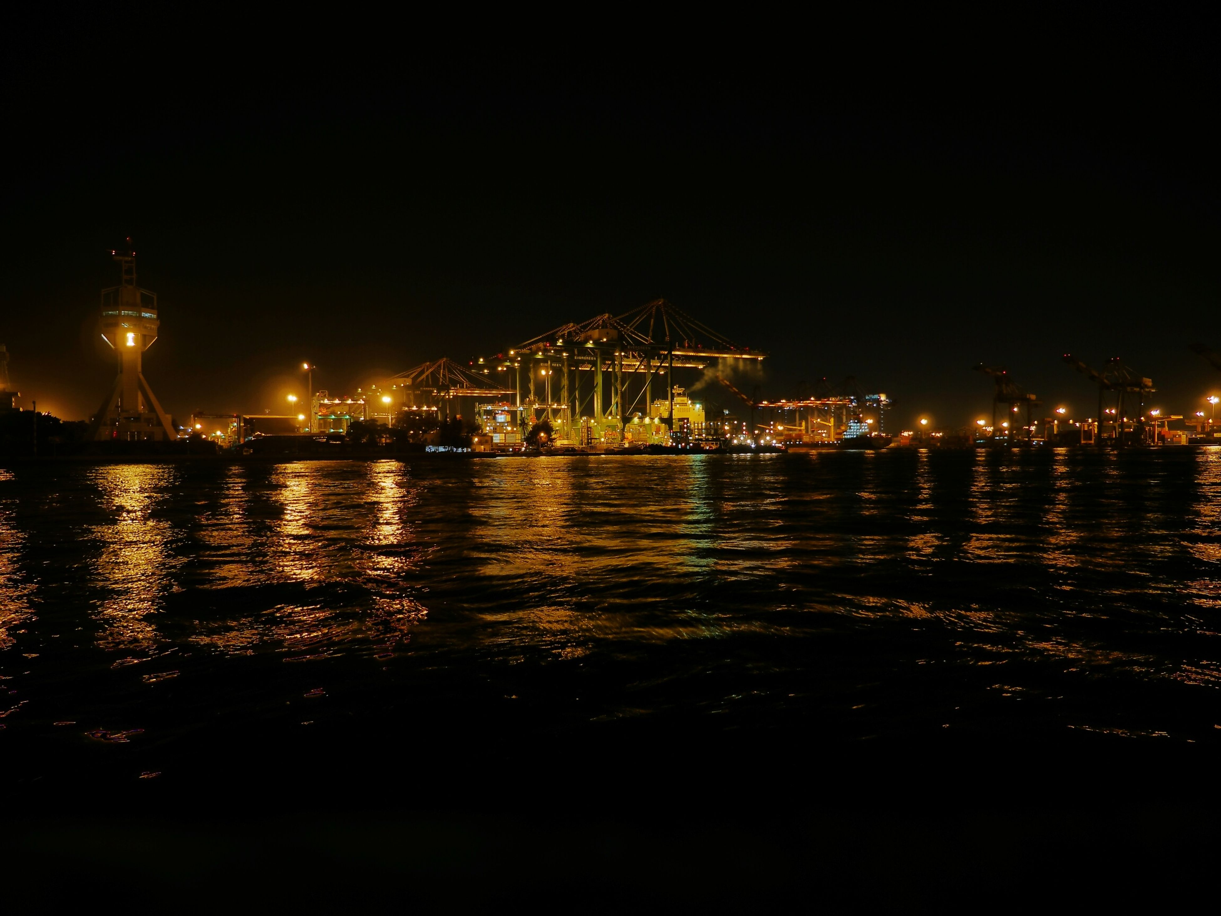 illuminated, night, water, building exterior, city, architecture, built structure, sea, waterfront, cityscape, river, reflection, copy space, nautical vessel, clear sky, sky, harbor, lighting equipment, city life, transportation