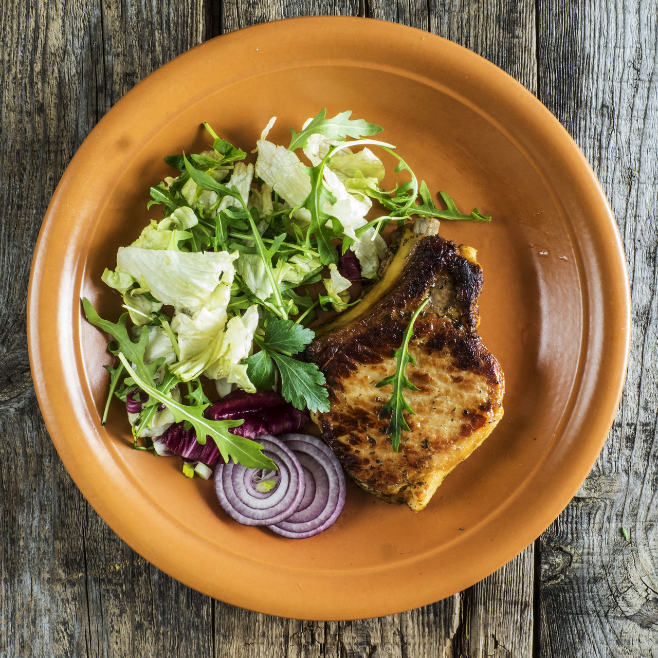 Roasted pork chop on a plate with a green salad, red onion on an old wooden weathered table Chop Close-up Day Food Food And Drink Freshness Green Healthy Eating Indoors  No People Old Onion Plate Pork Ready-to-eat Relaxing Roasted Salad Table Weathered Wood - Material Wooden