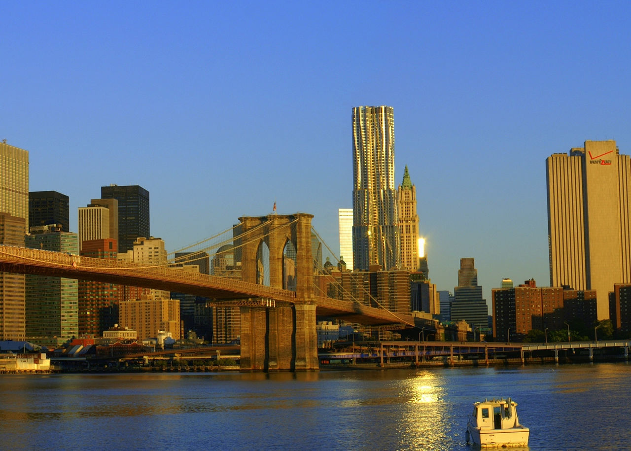 architecture, built structure, building exterior, city, connection, skyscraper, transportation, bridge - man made structure, clear sky, cityscape, river, waterfront, no people, outdoors, water, blue, modern, urban skyline, day, illuminated, sky
