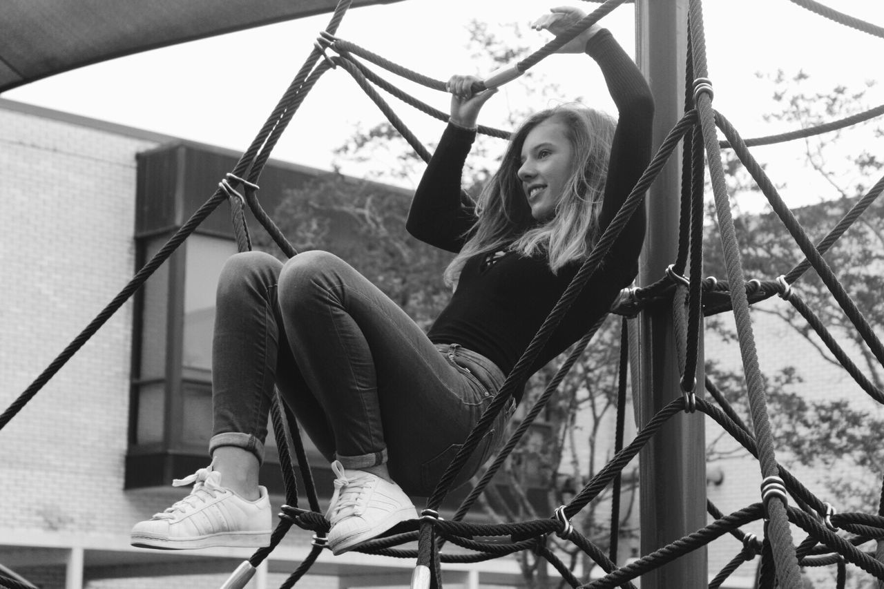 leisure activity, real people, sitting, casual clothing, one person, lifestyles, full length, railing, happiness, young women, day, young adult, smiling, outdoors, beautiful woman, people