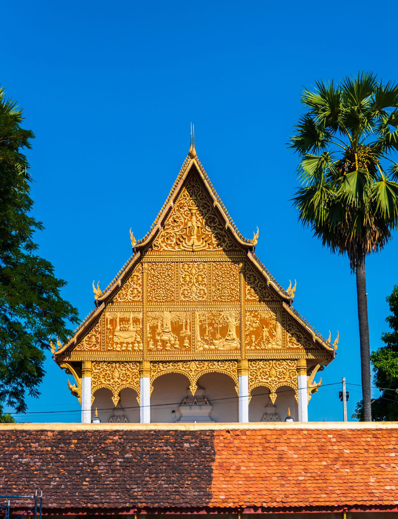 The holy temple of Buddhism in a bright sky atmosphere. Architecture Baked Clay Blue Buddhism Building Exterior Built Structure Chapel Clear Sky Day Gable Gold Colored Isosceles Low Angle View No People Outdoors Page Palm Tree Pattern Place Of Worship Roof Sanctuary  Sky Terracotta Tree