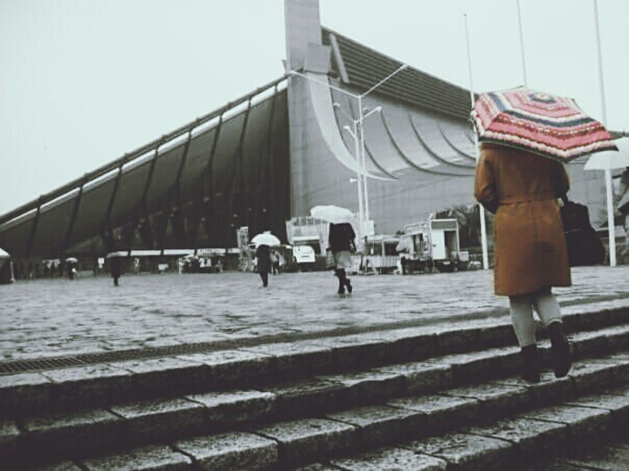 She acts like summer, and walks like rain.. ☔| 撮影地: Yoyogi National Stadium (Jinnan, Shibuya-ku, Tokyo) | 国立代々木競技場《東京都渋谷区神南》| Colorsplash Architecture by KenzoTange 丹下健三 国立代々木競技場第一体育館 Yoyogi National Gymnasium Real People Full Frame Umbrella☂☂ Winter Rain Built Structure Building Exterior Tokyo Cityscape City Life City View  Rear View Street Photography Color Splash Drastic Edit Edit Junkie EyeEm Gallery EyeEm Best Shots EyeEmNewHere EyeEm Best Shots - Architecture