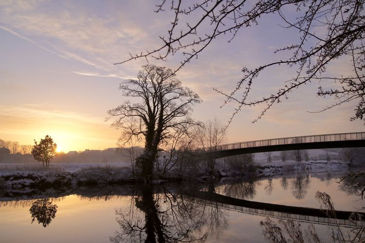 snowy scene by river at sunrise in wetherby Architecture Bare Tree Beauty In Nature Branch Bridge - Man Made Structure Built Structure Cloud - Sky Connection Day Foot Bridge Nature No People Outdoors Reflection River Scenics Sky Snow Sunrise Sunset Tranquil Scene Tranquility Tree Water Winter