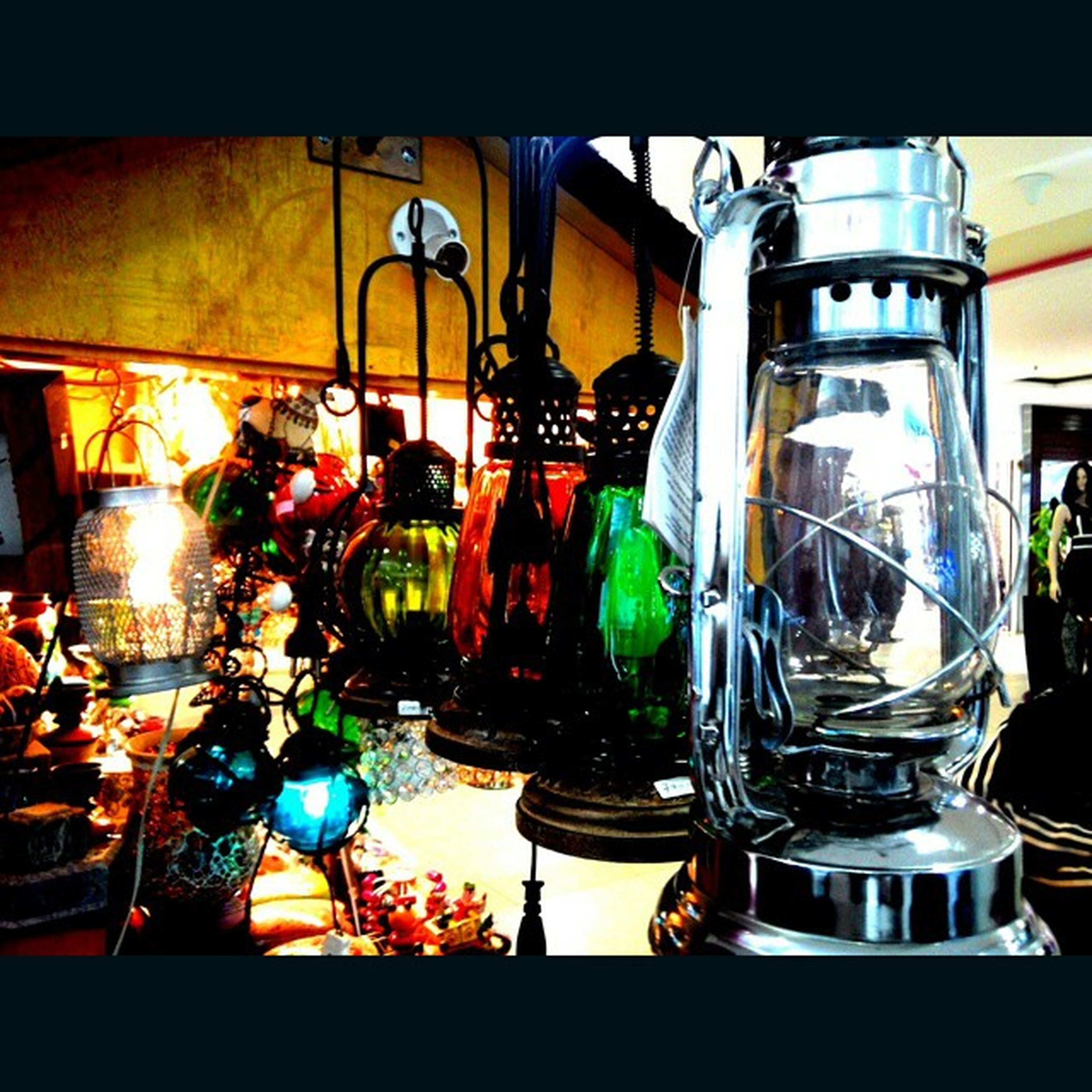 indoors, glass - material, still life, table, arrangement, large group of objects, illuminated, home interior, transparent, variation, shelf, bottle, lighting equipment, restaurant, hanging, no people, wineglass, drinking glass, candle, decoration