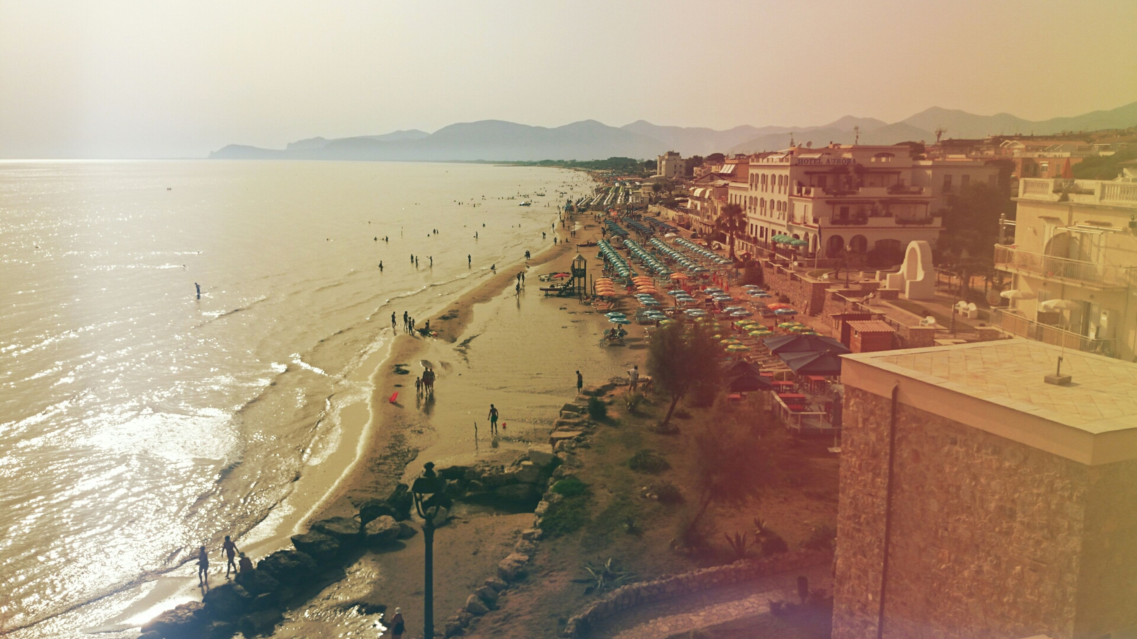 sea, water, beach, sand, shore, built structure, horizon over water, clear sky, architecture, building exterior, high angle view, incidental people, scenics, nature, sky, coastline, sunlight, vacations, tranquility, mountain