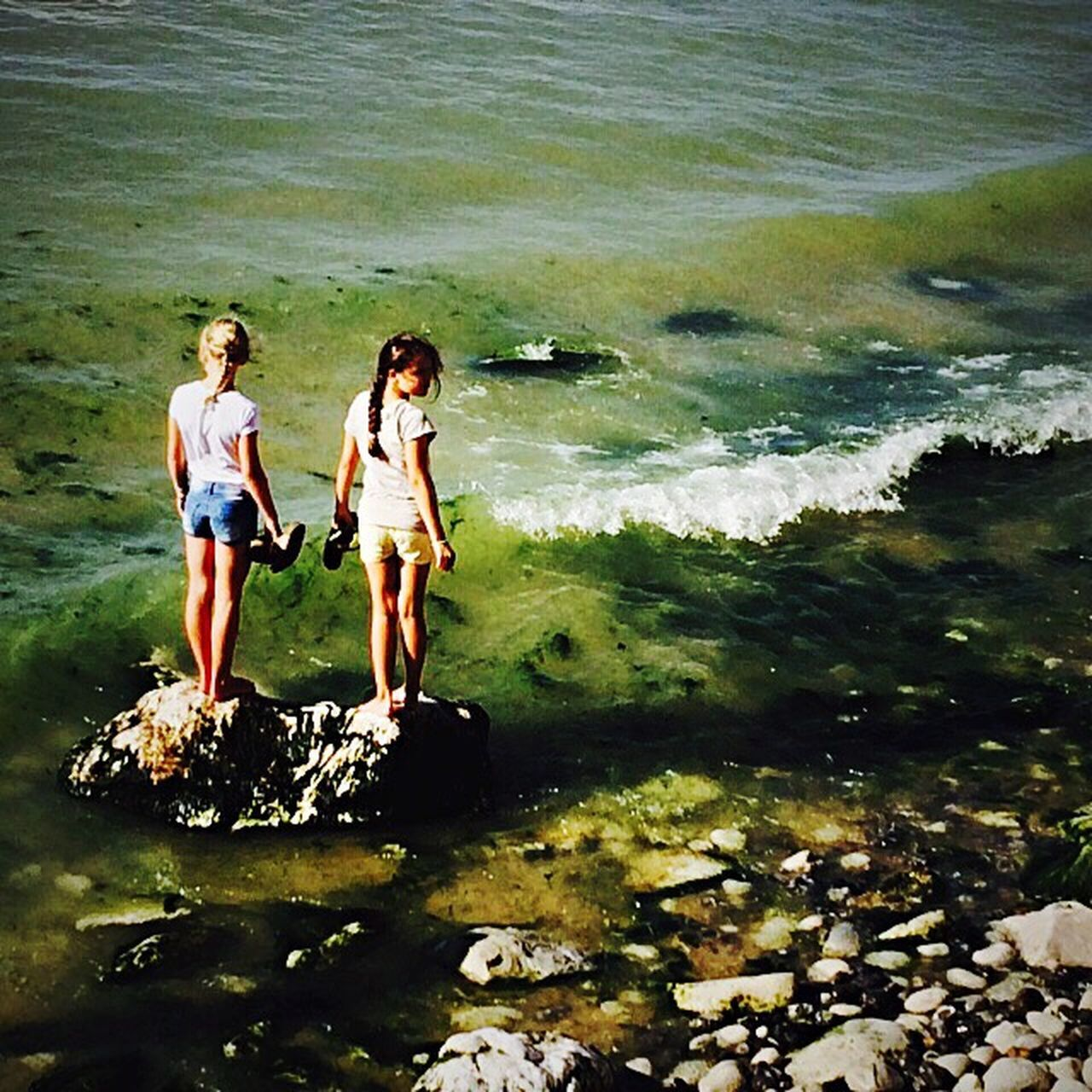 sea, water, nature, rock - object, vacations, adventure, full length, real people, day, togetherness, outdoors, leisure activity, beauty in nature, friendship, lifestyles, beach, two people, standing, ankle deep in water, wave, young adult