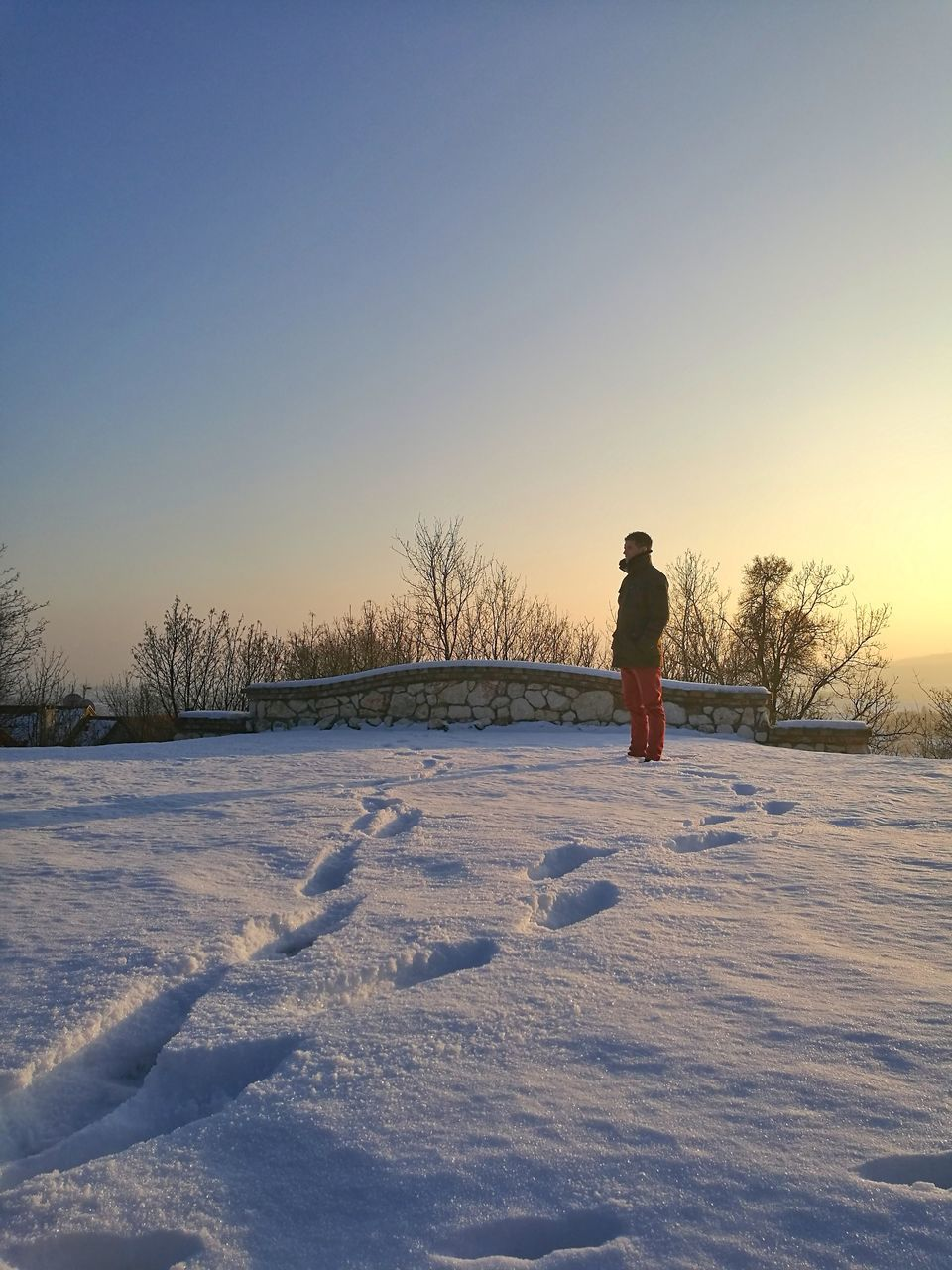 Side View Of Man Standing On Snow Covered Field Against Sky During Sunset