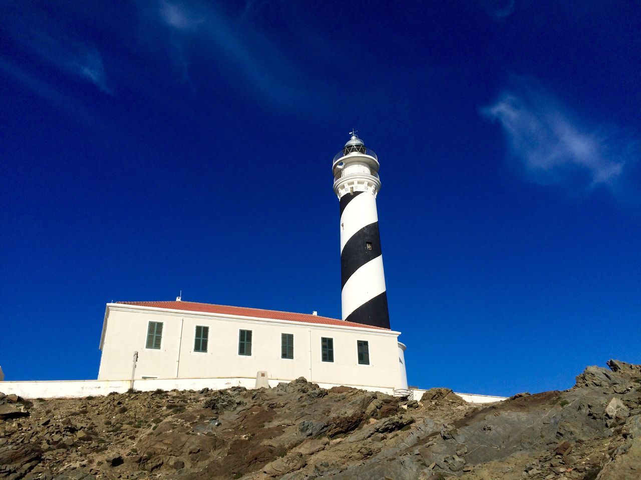 lighthouse, low angle view, architecture, blue, building exterior, built structure, day, no people, guidance, outdoors, nature, sky, clear sky, mountain