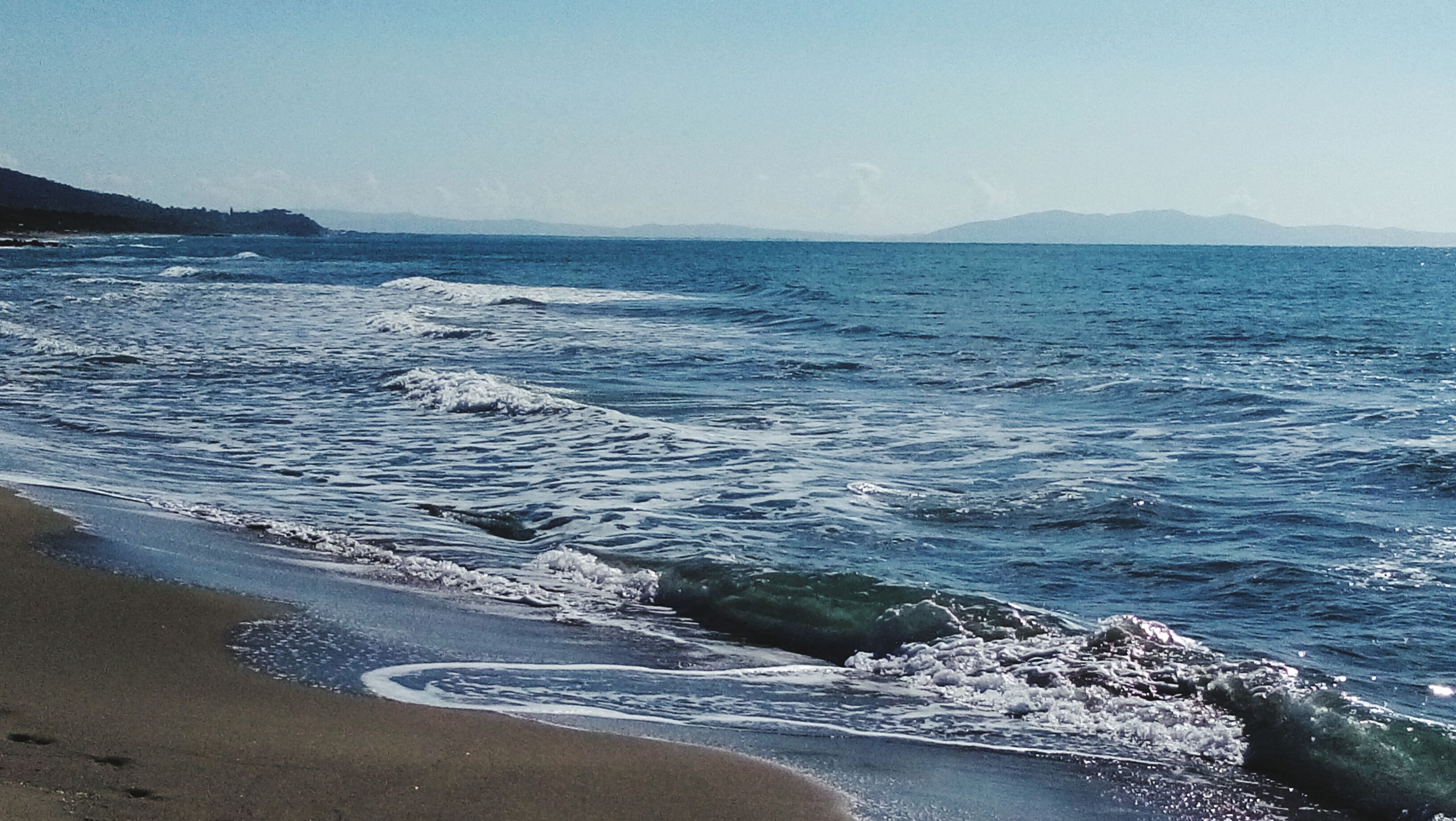 sea, water, beach, clear sky, tranquil scene, scenics, tranquility, beauty in nature, horizon over water, shore, copy space, coastline, nature, blue, sand, idyllic, wave, surf, mountain, rock - object