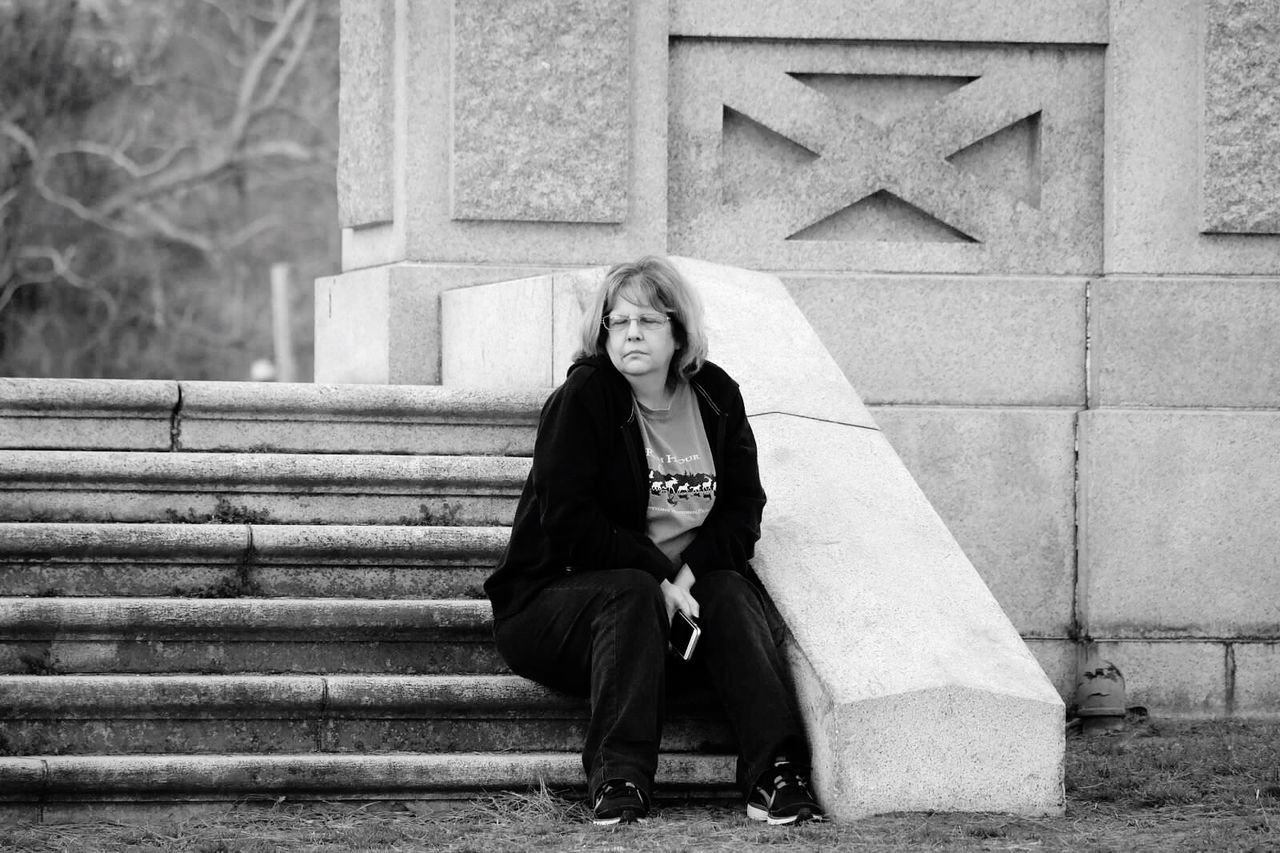 Full Length Of Mature Woman Sitting In Steps In Park
