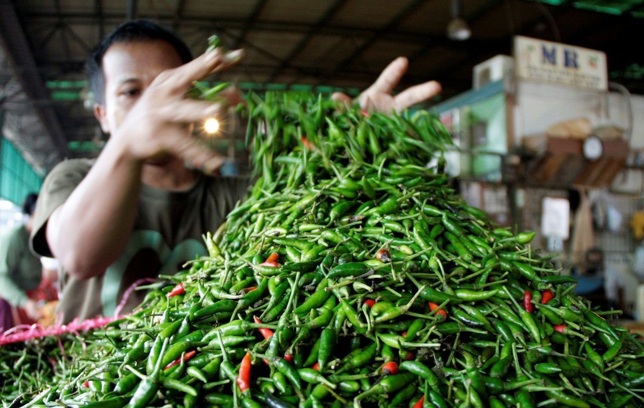 Man By Pile Of Green Chili Pepper In Market