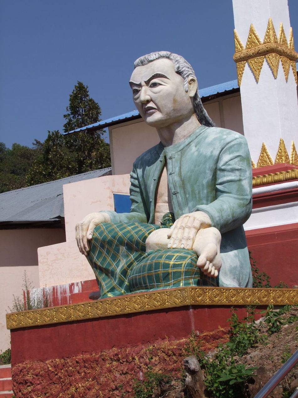 Statue of Benefactor for this Buddhist Pagoda BENEFACTOR Blue Sky Buddhist Art Buddhist Culture Buddhist Pagoda Buddhist Temple Composition Full Frame Human Representation Low Angle View Man Mount Popa Myanmar One Man Only Outdoor Photography Statue Statue Of A Man Sunlight Traditional Clothing Tree Unusual