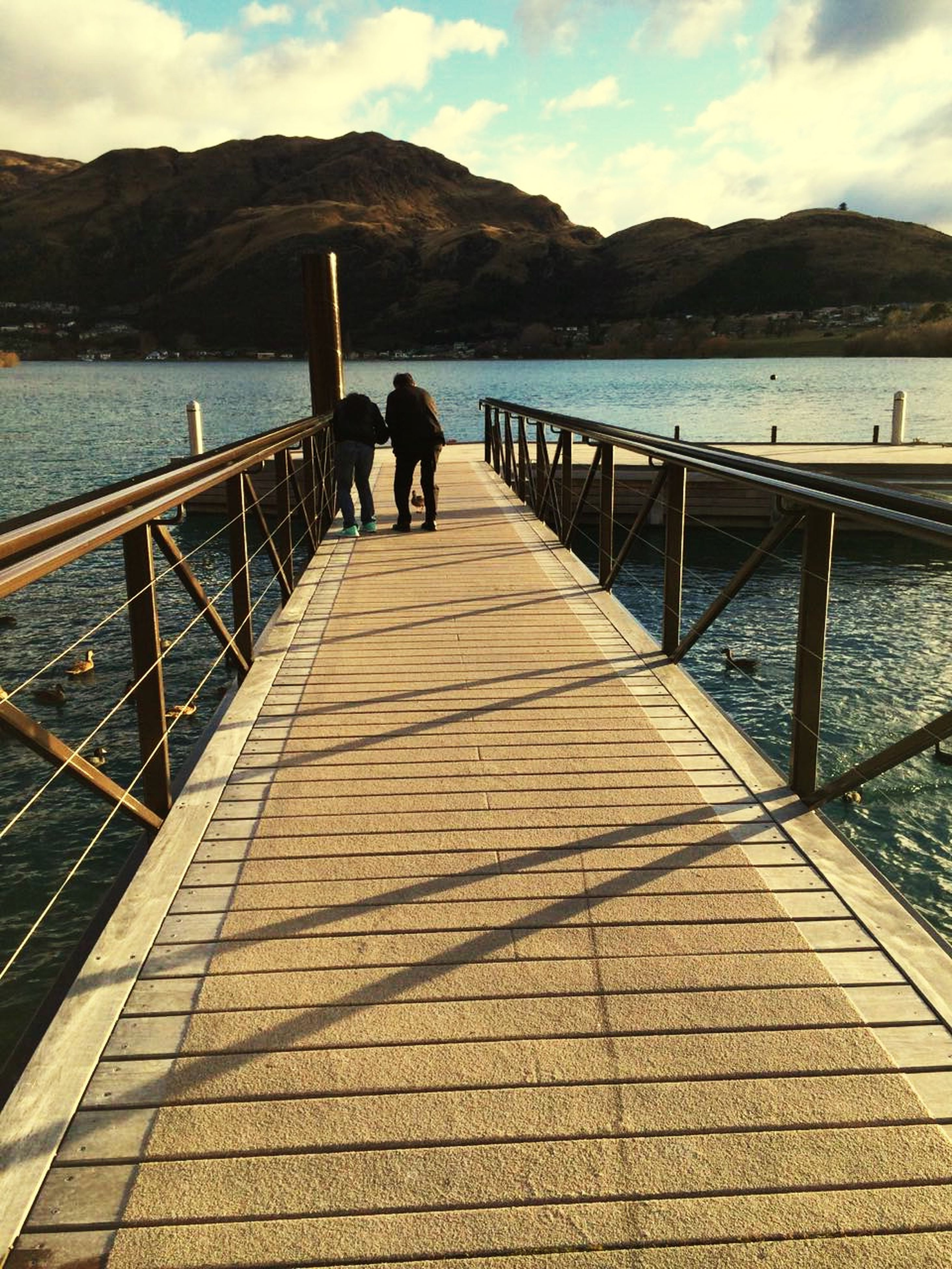 water, mountain, railing, leisure activity, lifestyles, men, pier, sky, rear view, person, full length, tranquil scene, tranquility, scenics, the way forward, beauty in nature, walking