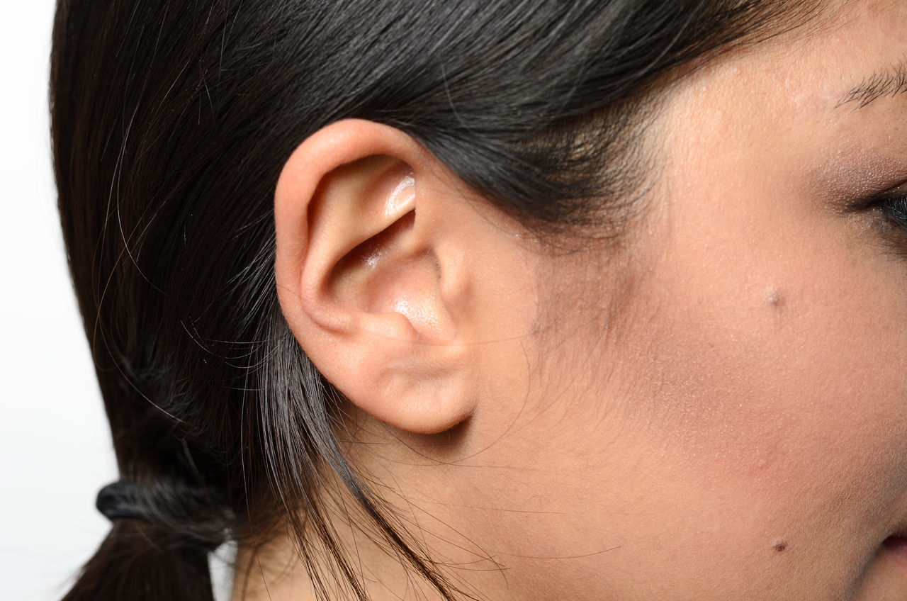 Close-Up Of Woman Ear Against White Background