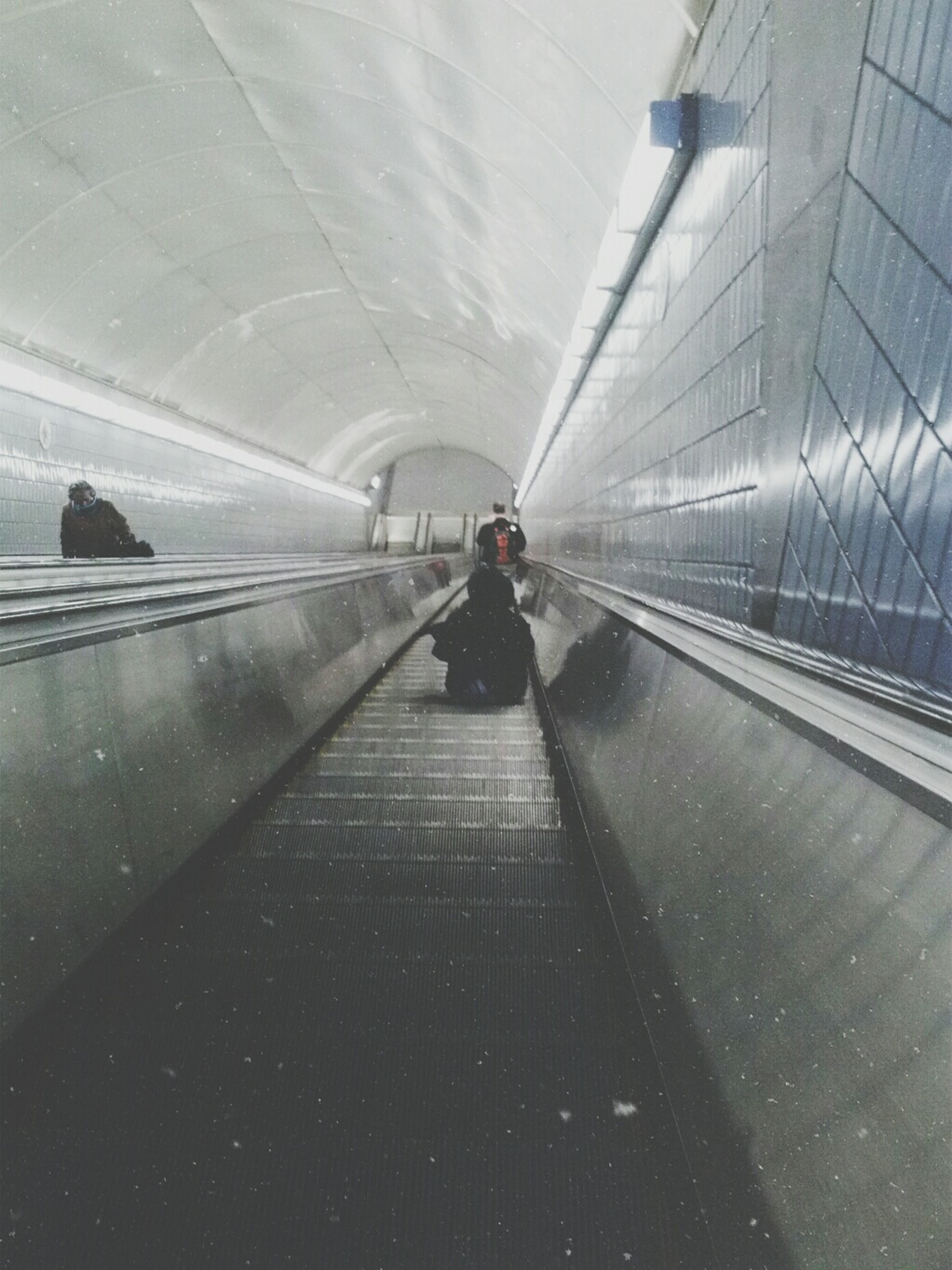 lifestyles, indoors, architecture, full length, walking, built structure, men, the way forward, rear view, tunnel, leisure activity, transportation, person, travel, standing, modern, city life, railing