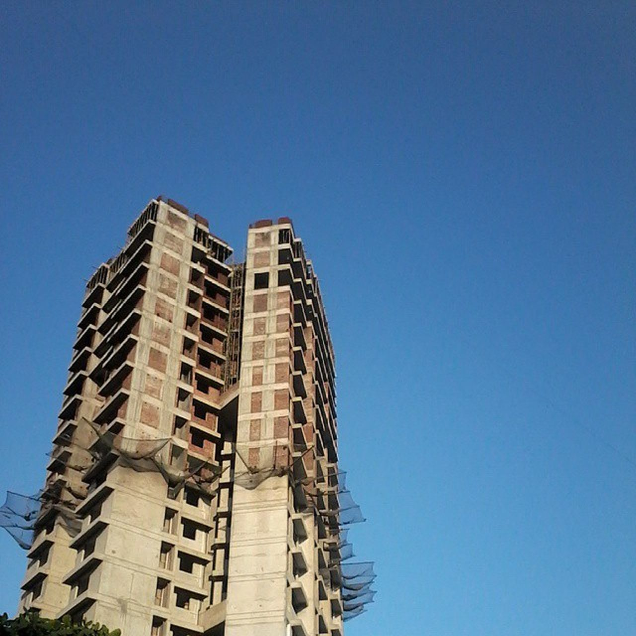 Low angle view of under construction building against clear blue sky Construction Construction Site Copy_Space Development Incomplete