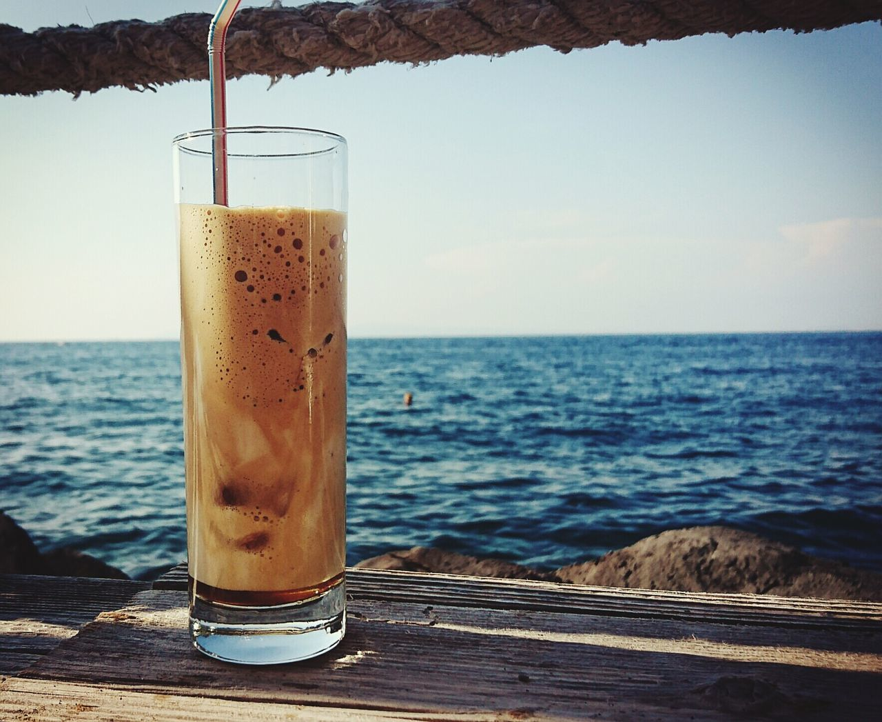 sea, drink, refreshment, water, food and drink, horizon over water, table, day, no people, outdoors, freshness, drinking glass, beach, sky, close-up, nature, beauty in nature