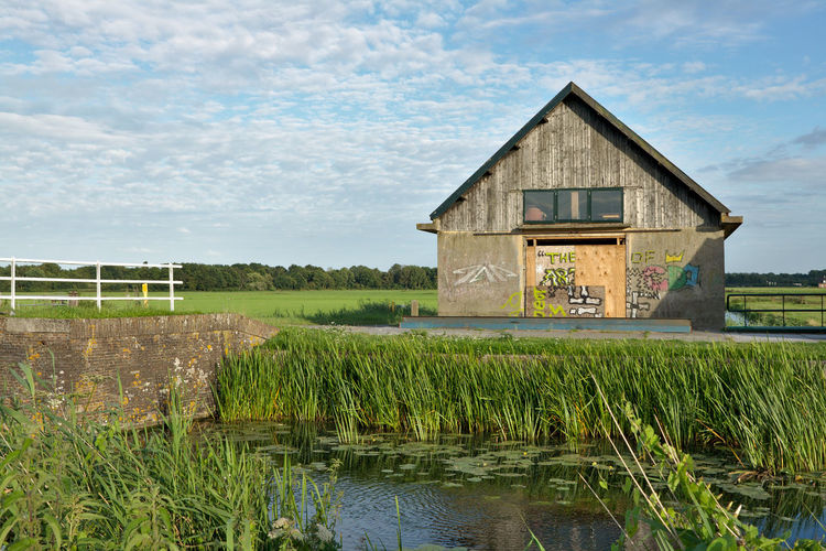 Graffiti Architecture Barn Building Exterior Built Structure Day Grass House Nature No People Outdoors Sky Water