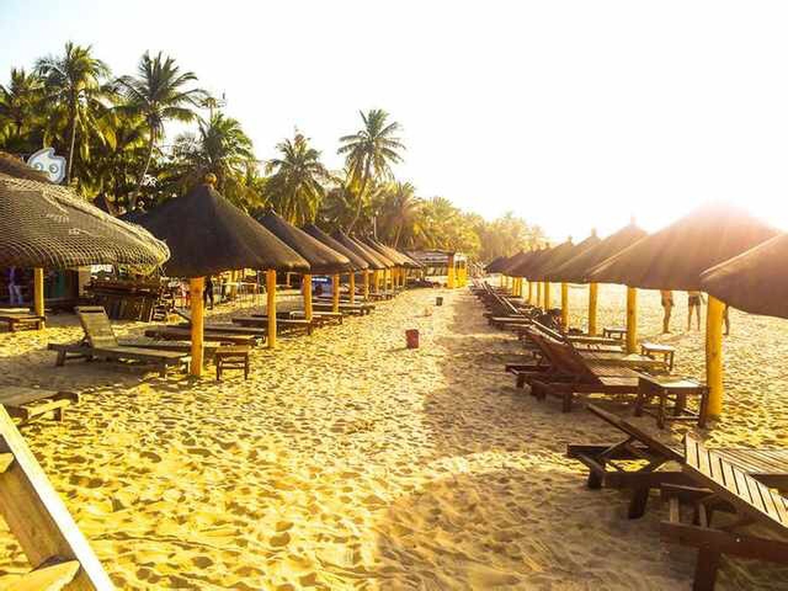 sand, beach, clear sky, palm tree, water, sea, shore, lounge chair, thatched roof, vacations, tranquility, sunlight, tranquil scene, tree, incidental people, beach umbrella, nature, wood - material, chair, parasol