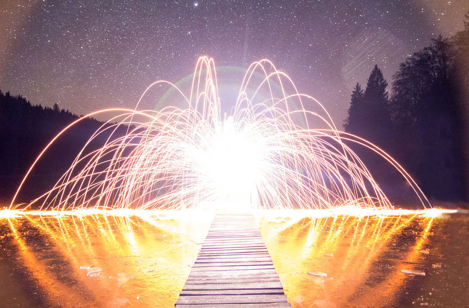 I really messed up the exposure, yet I think the shot looks kind of interesting with its flaring patterns ... But you decide! | Burning EyeEm Best Shots EyeEm Nature Lover Flare Illuminated Lake Light Long Exposure Longexposure Night No People Outdoors Overexposed Reflection Sky Skyscape Sparks Sparks Fly Star Star - Space Stars Steelwoolphotography Tree Wire Wool Wooden