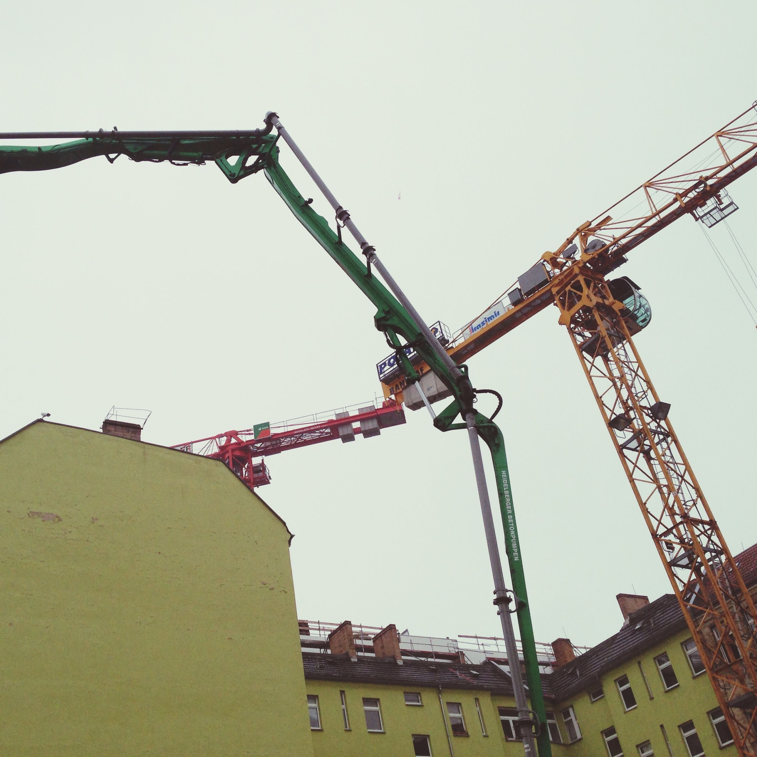 architecture, built structure, building exterior, low angle view, clear sky, construction site, crane - construction machinery, development, construction, residential building, copy space, crane, residential structure, building, industry, outdoors, no people, city, sky, incomplete