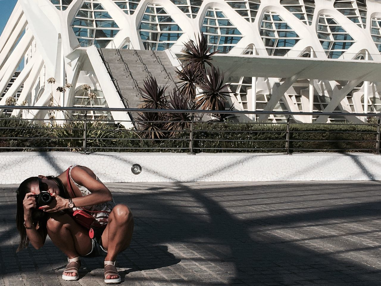 Woman Crouching On Walkway While Photographing During Sunny Day