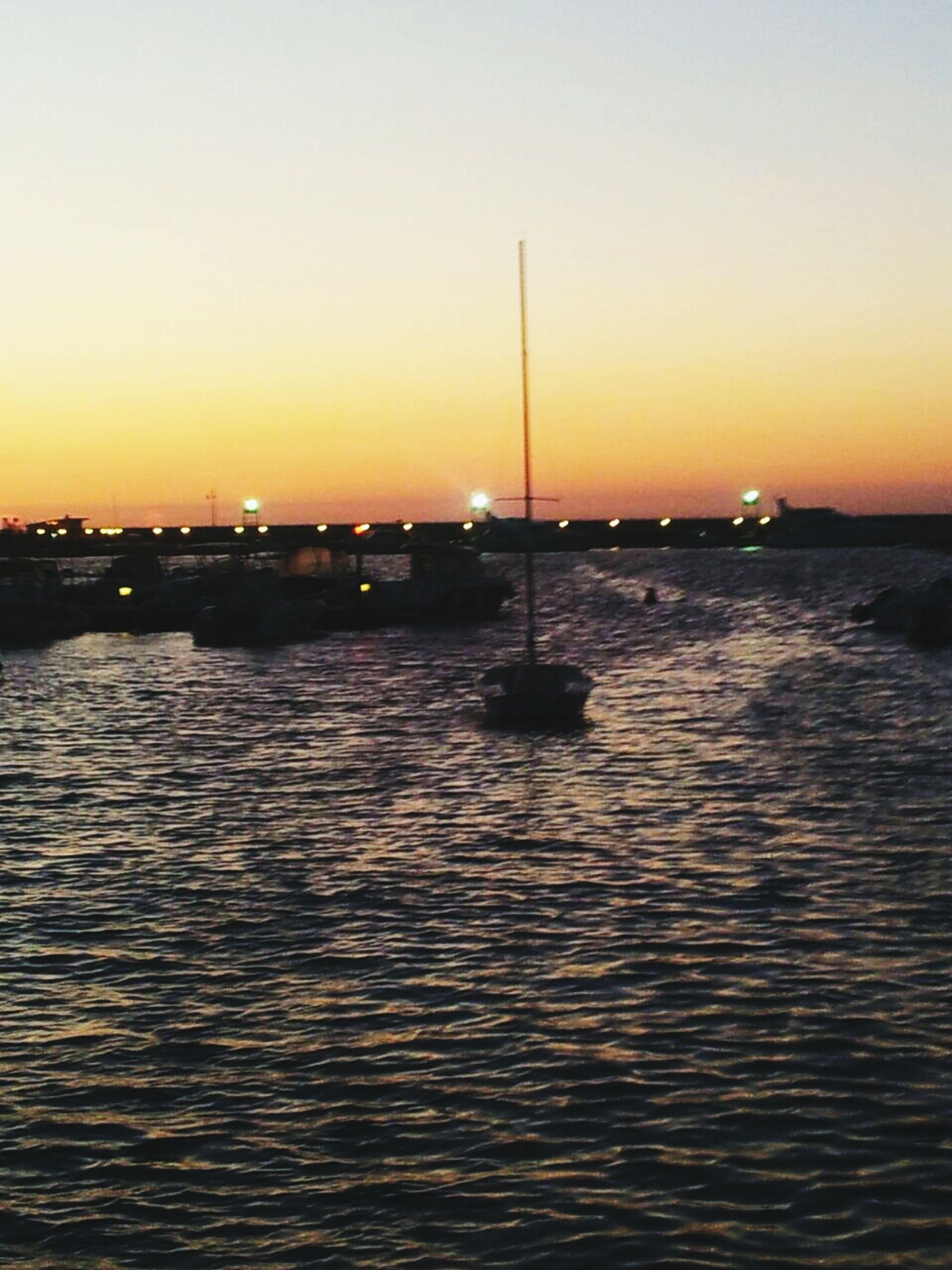 sunset, water, sea, clear sky, waterfront, orange color, copy space, scenics, transportation, tranquil scene, tranquility, rippled, beauty in nature, silhouette, nautical vessel, nature, idyllic, sky, reflection, dusk