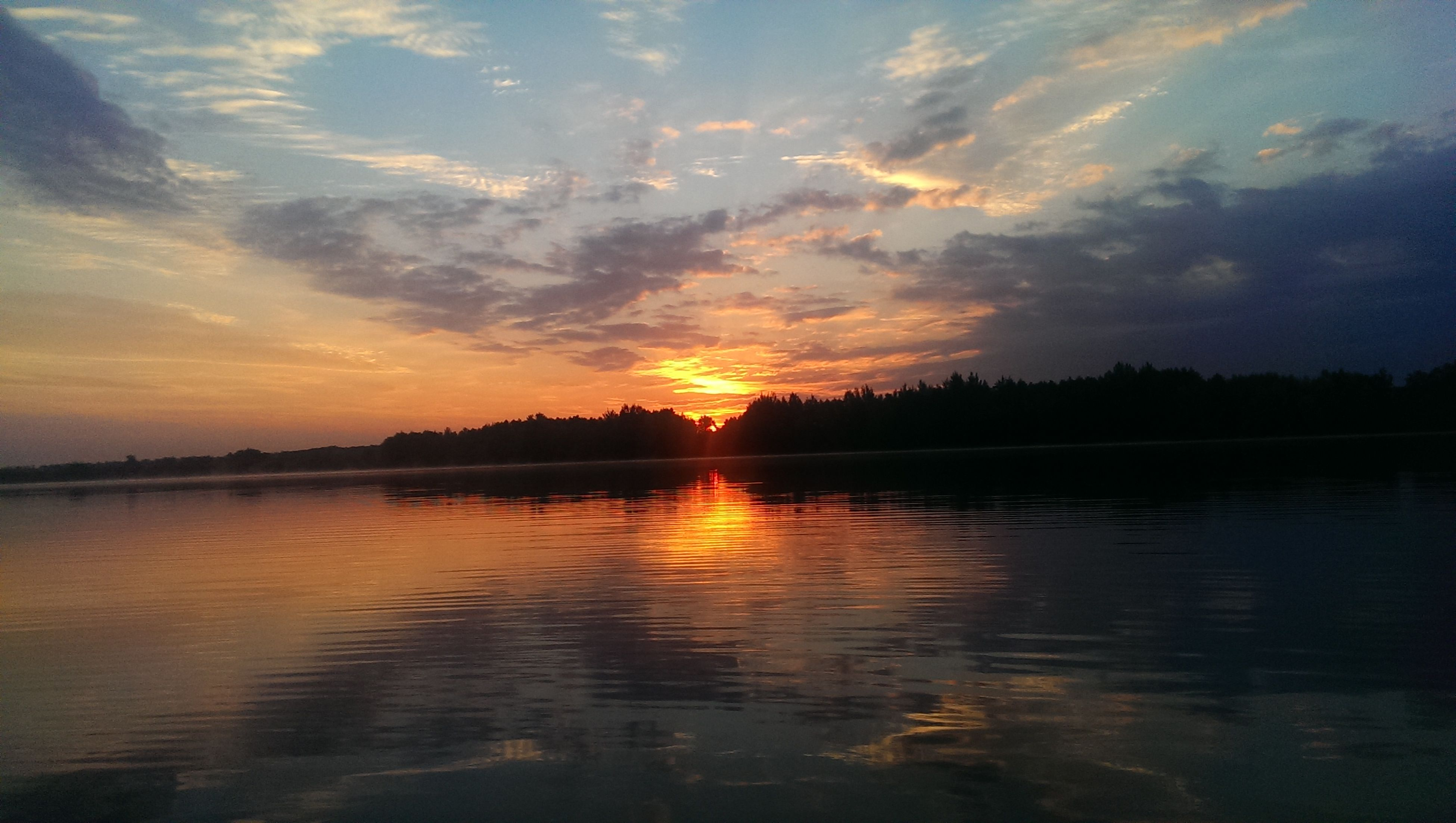 sunset, water, scenics, tranquil scene, lake, reflection, tranquility, beauty in nature, waterfront, orange color, calm, idyllic, sky, nature, sun, cloud - sky, cloud, dramatic sky, majestic, atmospheric mood, romantic sky, atmosphere, outdoors, moody sky, non-urban scene, no people, sea, vibrant color, standing water