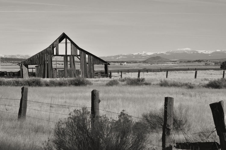 Old dilapidated wooden barn behind a fence with snow capped mountains in the background. Americana Barn California Canby Modoc County USA Architecture Black And White Built Structure Day Grass Landscape Mountain Nature No People Outdoors Sky Wire Fence Wooden Fence Posts
