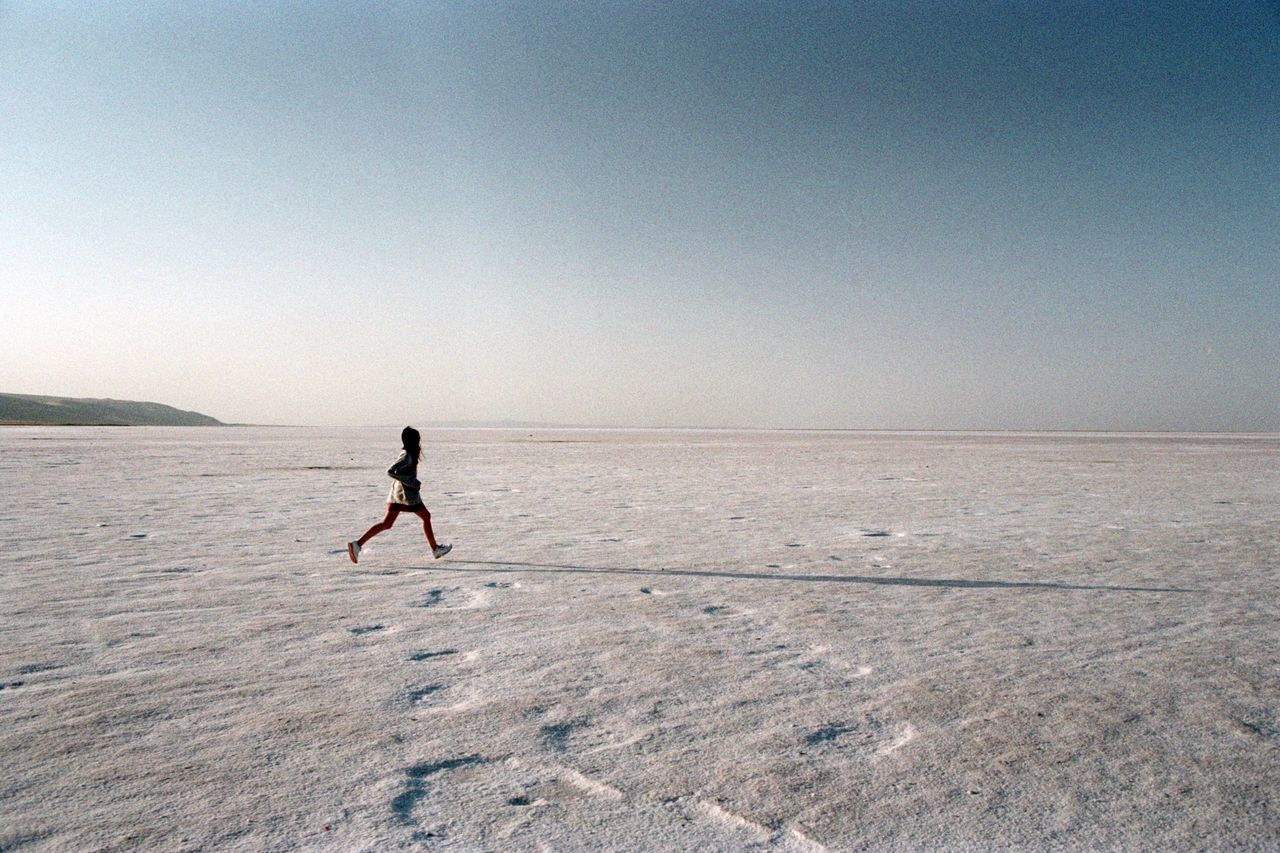 full length, clear sky, adventure, outdoors, day, desert, salt flat, landscape, horizon over land, one person, scenics, arid climate, salt - mineral, real people, nature, beauty in nature, salt basin, energetic, sky, people